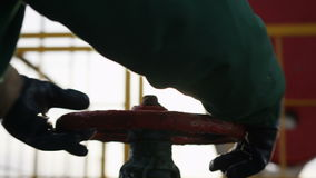 Closeup worker in leather gloves twists iron valve stock footage