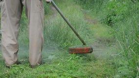 Closeup worker mow grass. Closeup worker man farmer cutting grass in garden with weed trimmer stock footage