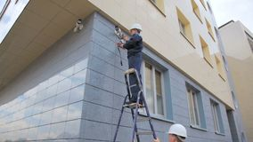 Worker checks CCTV camera operation and colleague holds ladder stock video footage