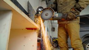 Closeup of worker using a grinder cuts metal in a workshop. stock footage