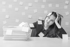 Closeup working woman are boring from hard work and pile of work paper in front of her in work concept on blurred wooden desk and royalty free stock photo