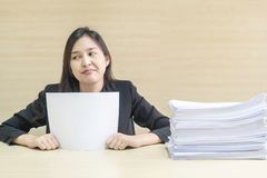 Closeup working woman are boring from pile of work paper in front of her in work concept on blurred wooden desk and wooden wall royalty free stock images