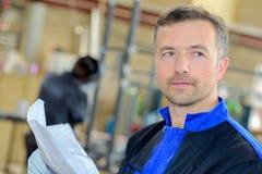 Closeup workman holding paperwork Stock Photo
