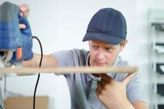 Closeup workman using jigsaw Stock Images