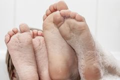 Closeup of wrinkled feet on edge of bubble bath. Closeup of wrinkeled feet on edge of bubble bathtub Stock Photos