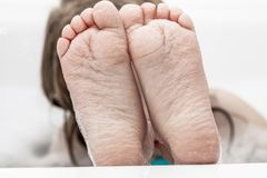 Closeup of wrinkled feet on edge of bubble bath. Closeup of wrinkeled feet on edge of bubble bathtub Royalty Free Stock Photo