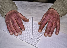 Closeup of the wrinkled hands of man holding pen and paper, wear Royalty Free Stock Photo