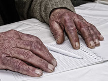 Closeup of the wrinkled hands of man holding pen and paper, wearing a green sweater Stock Images