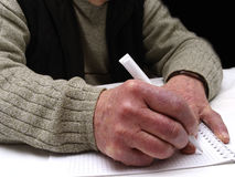 Closeup of the wrinkled hands of an old caucasian man holding pen and paper Royalty Free Stock Photo
