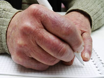 Closeup of the wrinkled hands of an old caucasian man holding pen and paper Stock Photography