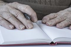 Closeup wrinkled hands of a person holding a pen royalty free stock photos
