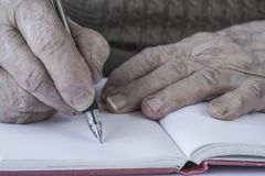 Closeup wrinkled hands of a person writing stock photos