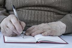 Closeup wrinkled hands of a person writing royalty free stock photos