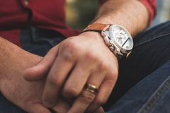 Closeup of wristwatch on arm of a young man outdoors in casual clothing. A young man sits on a bench in an outdoor park and checks his expensive wristwatch Stock Photography