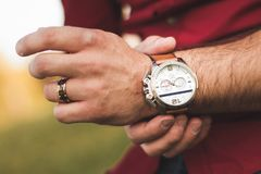 Closeup of wristwatch on arm of a young man outdoors in casual clothing. A young man in an outdoor park adjusts his expensive wristwatch Royalty Free Stock Photo