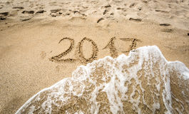Closeup of 2017 written on sand being washed off by wave Stock Images