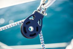 Closeup on yacht cord crank, rope holder. On white sail background stock photo