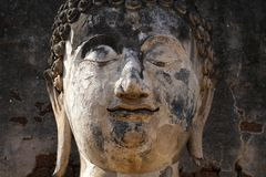 Closeup 400 years old of ancient stone buddha face statue in the forest, art crafting sculpture. Head, face, lobe, ear, hair, nose, backgrounds, wallpaper Royalty Free Stock Photos