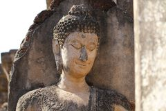 Closeup 400 years old of ancient stone buddha head statue in the forest, art crafting sculpture Stock Photography