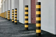 Yellow and black poles. Closeup of yellow and black steel bollards that restrict movement of cars Stock Photography
