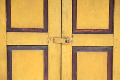Closeup yellow door with metal lock Royalty Free Stock Image
