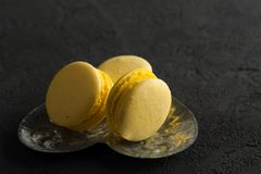 Closeup of yellow macaroons on black concrete. Background Royalty Free Stock Image
