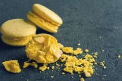 Closeup of yellow macaroons on black concrete background Royalty Free Stock Photography