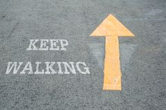 Closeup yellow painted arrow sign on cement street floor with white keep walking word textured background. Closeup yellow painted arrow sign on cement street royalty free stock photography