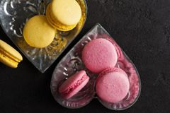 Closeup of yellow pink macaroons on black concrete Stock Photography