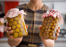 Closeup of yellow plums and gooseberries in glass jars stock images