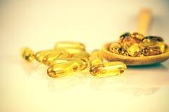 Closeup yellow soft gelatin supplement fish oil capsule Stock Photography