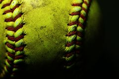 Yellow softball closeup with red seams on black background. Closeup of yellow softball with many red seams on black background stock photography