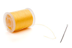 Closeup of a yellow spool of thread and a needle Royalty Free Stock Photos