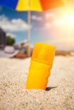 Closeup of yellow suntan lotion bottle lying on sand at beach Stock Image
