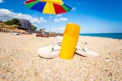 Closeup of yellow suntan lotion and flip flops lying on sandy be Stock Photos