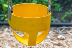 Closeup of yellow toddler baby swing part of a childrens swing set stock images