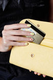 Closeup of yellow woman nails on a credit card Royalty Free Stock Photos
