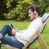 Closeup on young adult listening to music in green park. Closeup on an attractive bearded young student listening to music with headphones sitting on profile in Royalty Free Stock Photo