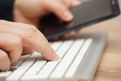 Closeup of young adult working on computer and using smart mobil Stock Photography