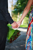 Closeup of young affectionate couple holding hands in a summer p Stock Photography