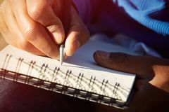 Closeup of young american african man making notes in copybook. Male student writing new ideas at paper pad. Closeup of young american african man making notes Royalty Free Stock Photography