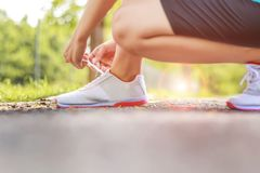 Closeup young asian female runner tying her shoes preparing for. A run a jog outside Royalty Free Stock Photos