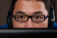 Closeup of young asian man playing on computer Royalty Free Stock Photos