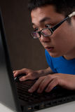 Closeup of young asian man working on laptop Royalty Free Stock Photography