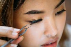 Asian woman placing decorative eyelashes on eye. Closeup young Asian model placing decorative eyelashes on eye on blurred background royalty free stock image
