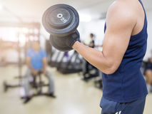 Closeup of a young athlete man lifting weights. At sport club Stock Photo