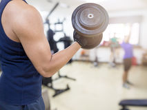 Closeup of a young athlete man lifting weights. At sport club Stock Images