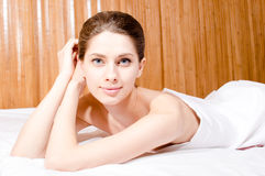 Closeup on young attractive blue eyes woman lying in spa & looking at camera Royalty Free Stock Images