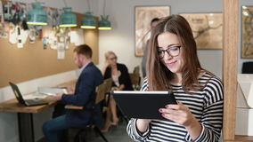 closeup young attractive brunette businesswoman uses a touchscreen tablet in the modern startup office. Closeup attractive brunette businesswoman uses a Stock Photo