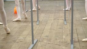Closeup , Young ballerina legs in ballet shoes, pointes, in beige leotards, perform exercises near barre, on an old stock video